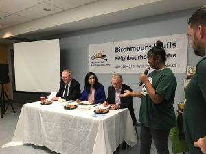 Student explaining their dish to the three challenge judges MP Bill Blair, MPP Doly Begum, and yours truly